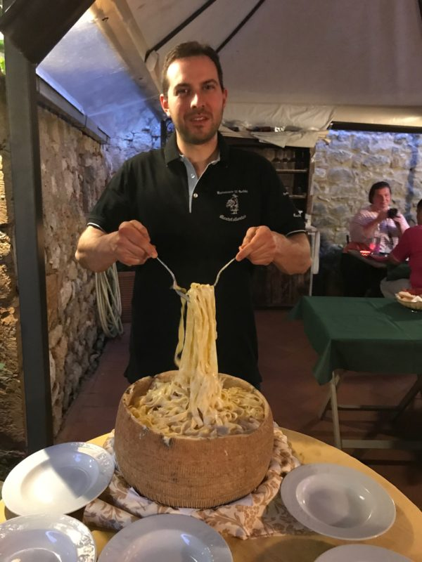 tossing pappardelle in a parmesan wheel at an Italian cooking school