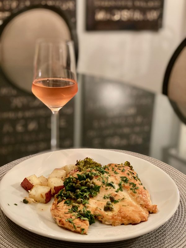 a dish of Chicken Piccata and glass of rosé